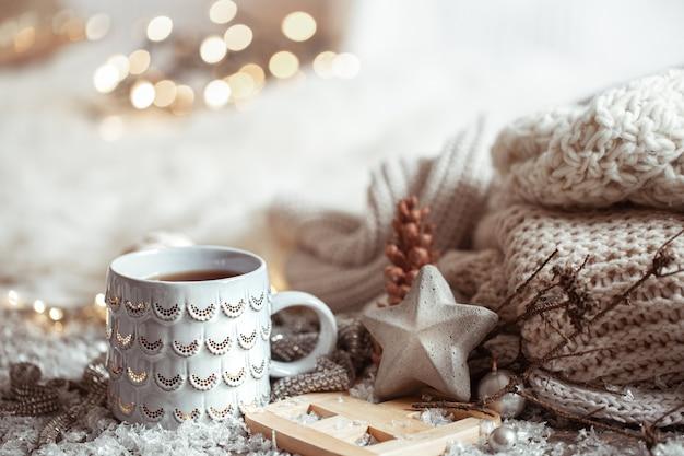 Piękny świąteczny kubek z gorącym napojem na jasnym tle niewyraźne. pojęcie domowego komfortu i ciepła.