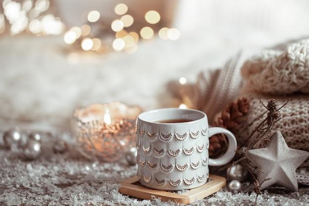 Piękny świąteczny kubek z gorącym napojem na lekkiej niewyraźnej ścianie. pojęcie domowego komfortu i ciepła.