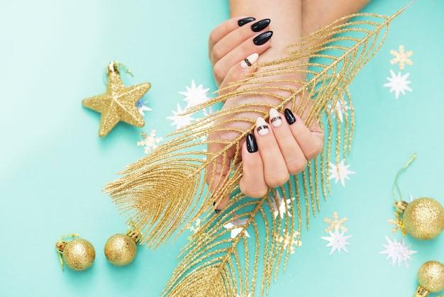 Piękny świąteczny manicure kobiecy. kobiece ręce trzymają mały prezent. zawartość noworoczna, bale, cekiny, gwiazdki. wesołych świąt