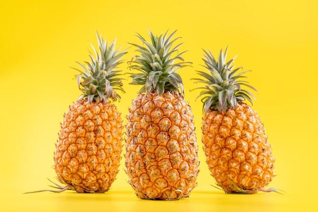 Piękny świeży ananas na białym tle na jasnym żółtym tle, lato sezonowe owoce projekt pomysł wzór koncepcja, miejsce na kopię, z bliska