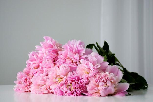Piękny świeży bukiet ciętych pastelowych różowych kwiatów piwonii w pełnym rozkwicie