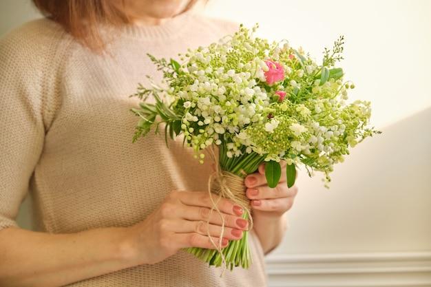 Piękny świeży bukiet kwiatów konwalii, różowa róża, zielone gałęzie w ręce kobiety