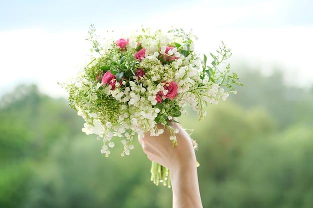 Piękny świeży bukiet kwiatów konwalii, różowej róży, zielonych gałęzi w ręce kobiety