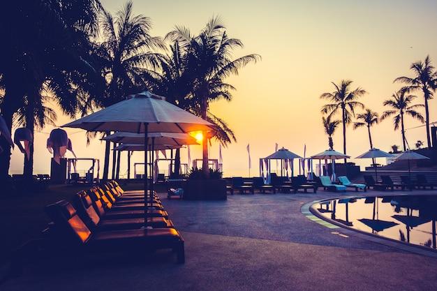 Piękny sylwetki drzewko palmowe z parasolem i krzesłem