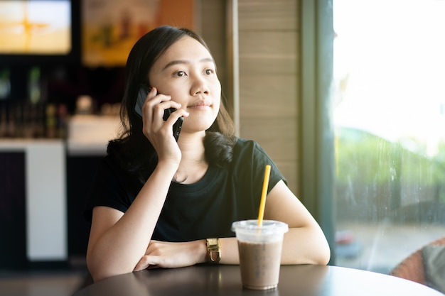 Piękny szczęśliwy azjatycki kobiety obsiadanie przy sklep z kawą i restauracją, kobieta patrzeje daleko od