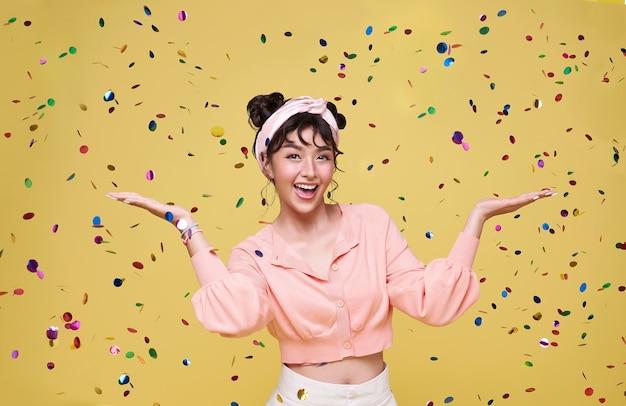 Piękny szczęśliwy azjatyckie kobiety nastolatki na party uroczystości z konfetti spada. koncepcja z okazji sylwestra lub urodziny.