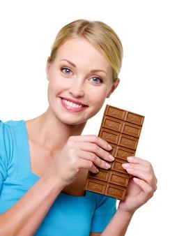 Piękny szczęśliwy blond kobieta trzyma słodki czarny pasek czekolady w pobliżu jej twarzy