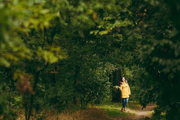 Piękny szczęśliwy kaukaski młody uśmiechający się brązowe włosy kobieta w żółtym płaszczu, dżinsy, buty w zielonym lesie. moda modelki ze złotymi liśćmi jesienią stojąc i spacerując w parku wczesną jesienią na zewnątrz.