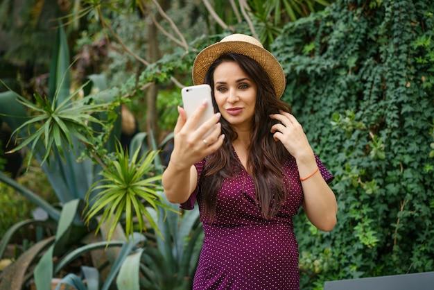 Piękny szczęśliwy kobieta w ciąży bierze selfie na smartphone na zielonym tle