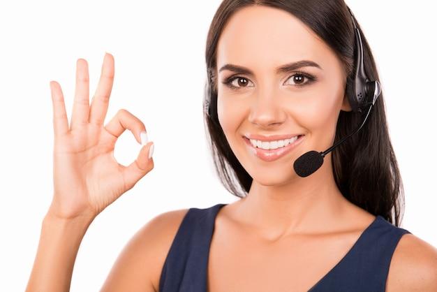 Piękny szczęśliwy konsultant z mikrofonem i słuchawkami pokazuje ok
