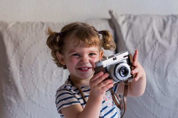 Piękny szczęśliwy małej dziewczynki obsiadanie na łóżku i używać rocznik kamerę. koncepcja domu, domu. styl życia