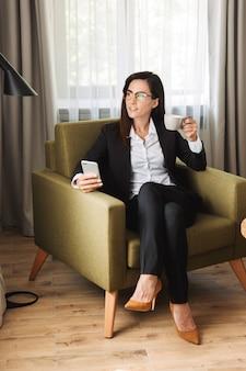 Piękny szczęśliwy młody biznes kobieta w wizytowym ubrania w pomieszczeniu w domu przy użyciu telefonu komórkowego picia kawy.