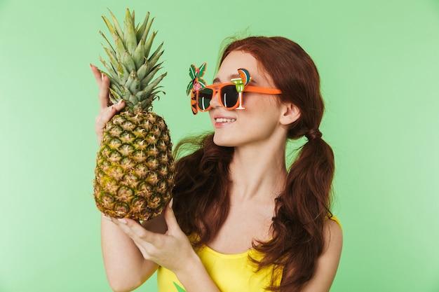 Piękny szczęśliwy młody rude dziewczyny pozowanie na białym tle na tle zielonej ściany gospodarstwa ananas.