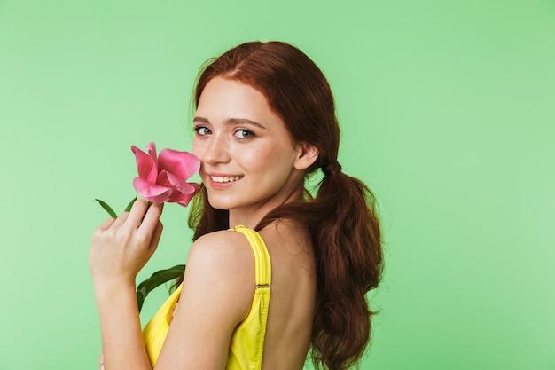 Piękny szczęśliwy młody rude dziewczyny pozowanie na białym tle na tle zielonej ściany gospodarstwa kwiat.