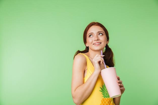 Piękny szczęśliwy młody rude dziewczyny pozowanie na białym tle na tle zielonej ściany picia koktajl.