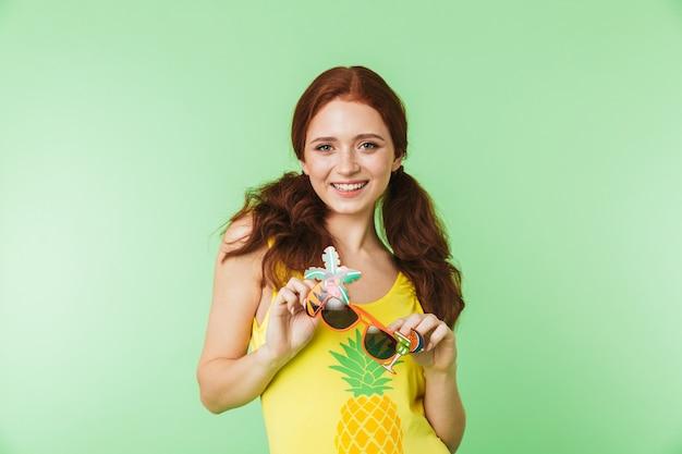 Piękny szczęśliwy młody rude dziewczyny pozowanie na białym tle na tle zielonej ściany.