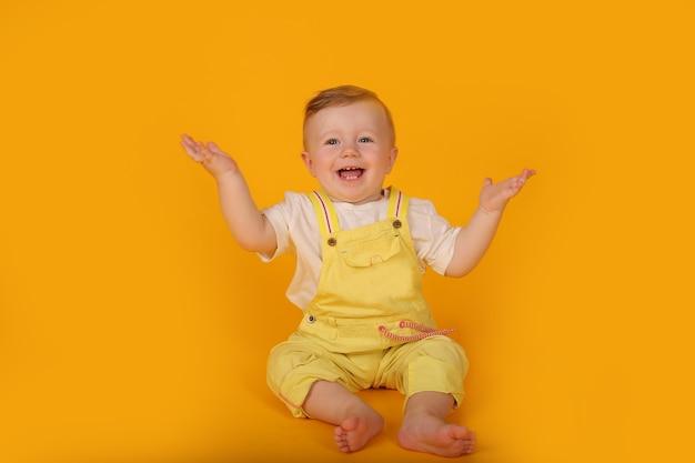 Piękny szczęśliwy niebieskooki chłopiec w żółtym garniturze rozłożył ręce po bokach