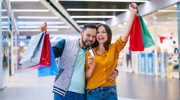 Piękny szczęśliwy podekscytowany para zakochanych lub rodziny z papierowymi torbami w ręce podczas spaceru podczas zakupów w centrum handlowym