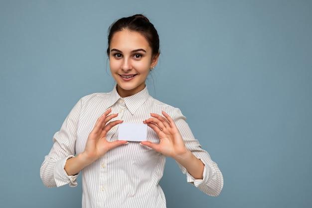 Piękny szczęśliwy pozytywny uśmiechnięty młoda brunetka kobieta ubrana w białą koszulę