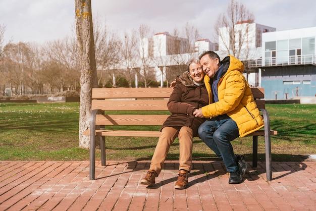 Piękny szczęśliwy starszy para siedzi na ławce w parku w słoneczny zimowy dzień