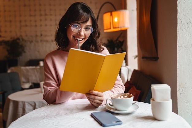 Piękny szczęśliwy uśmiechający się brunetka młoda kobieta pomieszczeniu w kawiarni czytanie książki.