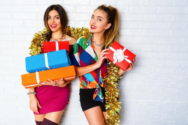Piękny szczęśliwy uśmiechnięty najlepsi przyjaciele trzymający prezenty i prezenty na przyjęcia. noszenie modnych ciuchów i złotego świecidełka