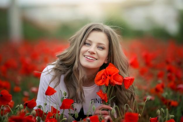 Piękny szczęśliwy uśmiechnięty nastoletni dziewczyna portret z czerwonymi kwiatami na głowie cieszy się w maczka pola natury tle. makijaż i kręcone fryzury. styl życia.