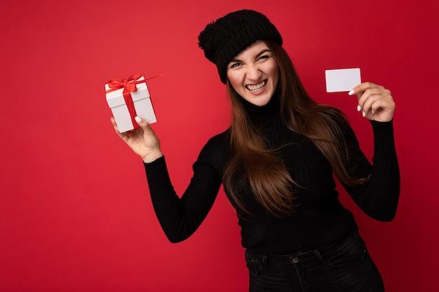 Piękny szczęśliwy zabawny zły młoda brunetka kobieta ubrana w czarny sweter i kapelusz na białym tle na czerwonym tle, trzymając kartę kredytową i pudełko patrząc na kamery