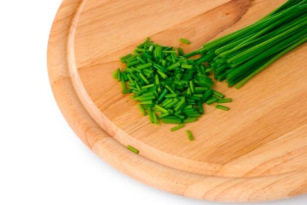 Piękny szczypiorek zielonej cebuli na desce na białym tle