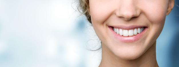 Piękny szeroki uśmiech młodej świeżej kobiety z wielkimi zdrowymi białymi zębami. na białym tle nad tłem