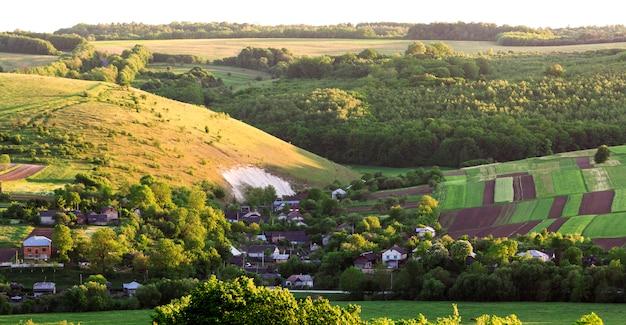 Piękny szeroki widok z lotu ptaka małej wioski wśród zielonych ogrodów, łatana panorama ciemnych zaoranych i zielonych pól i lasu w jasny letni dzień. piękno przyrody, rolnictwa i koncepcji rolnictwa.