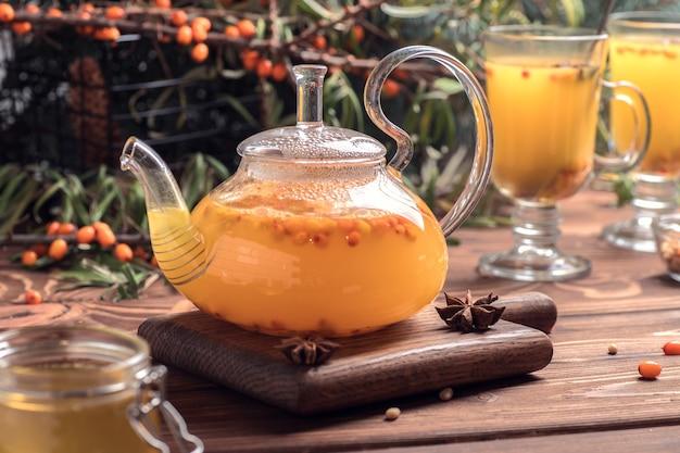Piękny szklany imbryk z herbatą z rokitnika. gorące napoje zimowe.