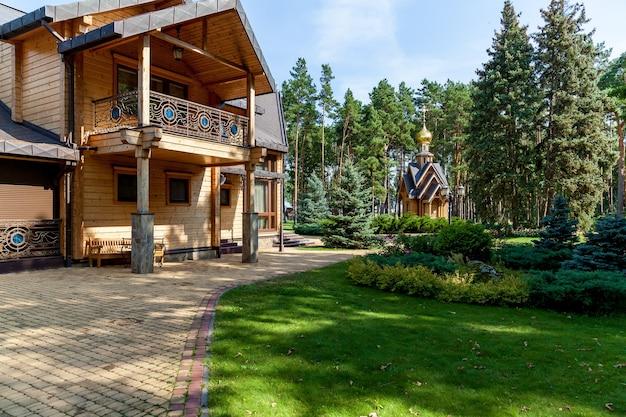 Piękny teren wypoczynkowy w lesie z nowoczesnym drewnianym domem i mnóstwem zielonych drzew w słoneczny letni dzień.