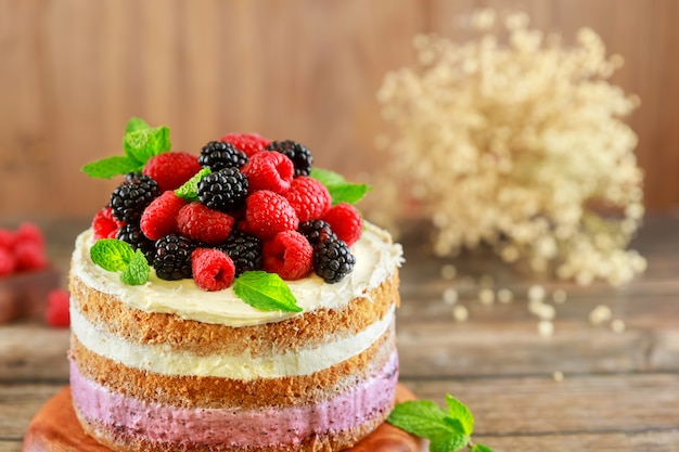 Piękny tort jagodowy ozdobiony świeżymi malinami i jeżynami na podłoże drewniane.