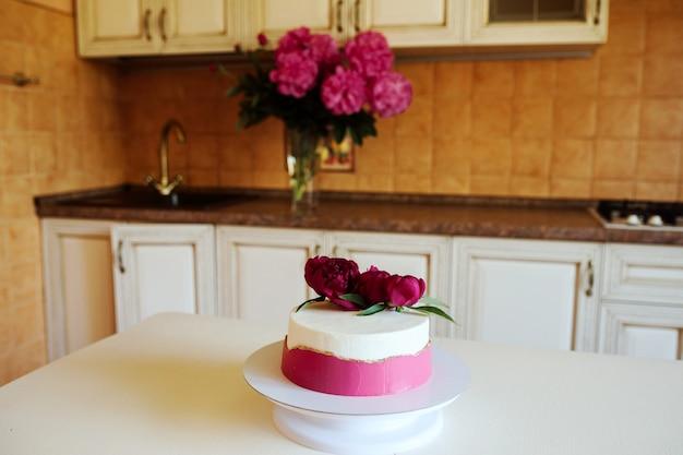 Piękny tort ozdobiony różowym kremem i peoies leży na kuchennym stole w pomieszczeniu.