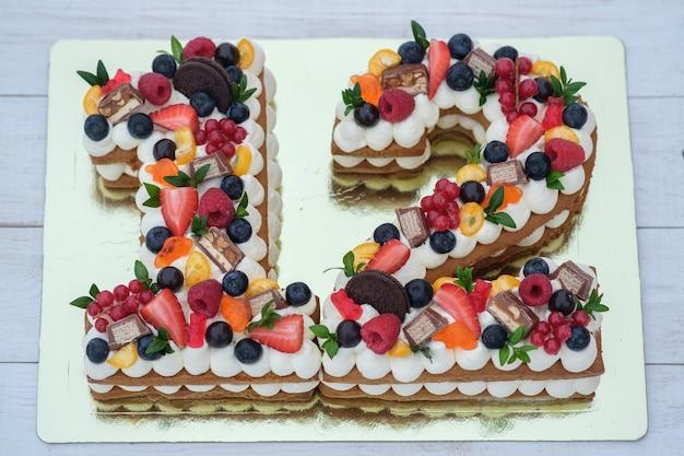 Piękny tort urodzinowy w kształcie cyfry dwanaście na złotym podłożu widok z góry