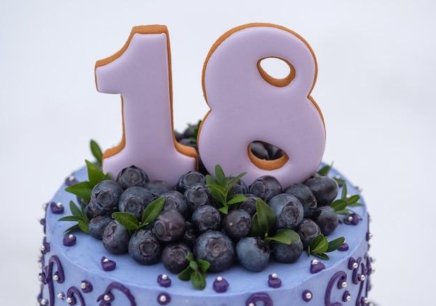 Piękny tort urodzinowy w liliowej tonacji z numerem osiemnaście z naturalnymi jagodami