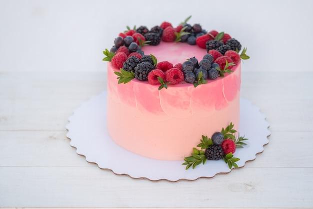 Piękny tort urodzinowy z jeżynami i jagodami na białym tle