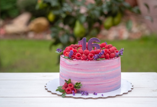 Piękny tort urodzinowy z liczbą szesnaście, ozdobiony malinami i kwiatami lawendy