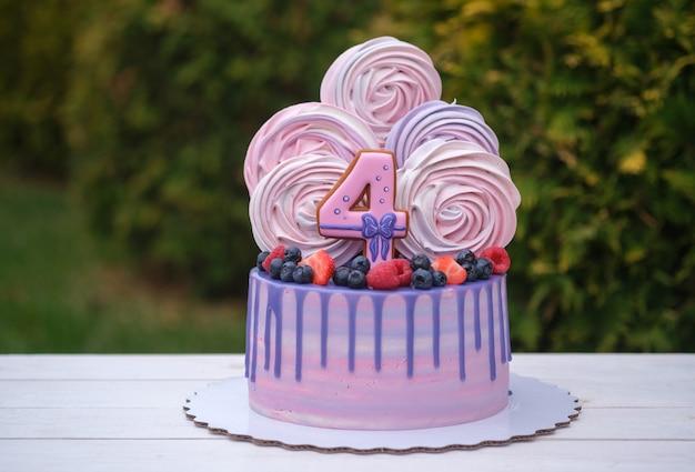 Piękny tort urodzinowy z numerem cztery, świeże jagody i ciasta bezowe