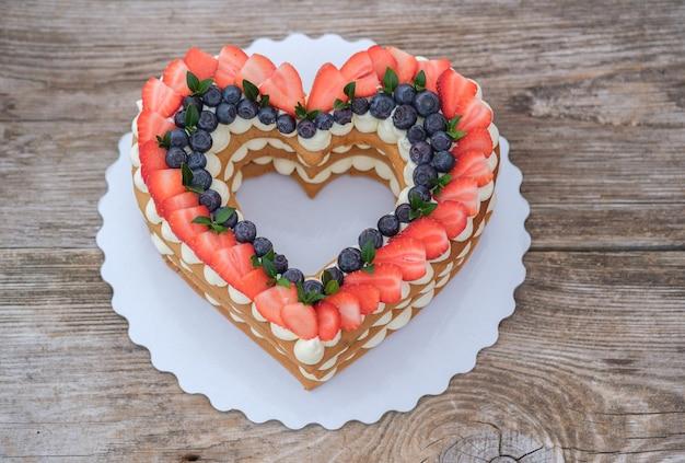 Piękny tort w kształcie serca ozdobiony świeżymi truskawkami, widok z góry na podłoże drewniane. tort walentynkowy, tort weselny