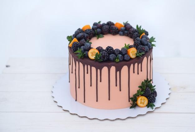 Piękny tort w stylu zimowym z gałązkami jodły i naturalnymi jagodami