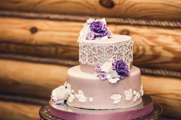 Piękny tort weselny w fioletowej tonacji, ozdobiony koronką i kwiatami