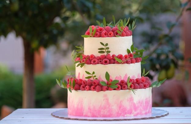 Piękny tort weselny w trzech poziomach z biało-różową śmietanką, udekorowany świeżymi malinami, w letnim ogródku