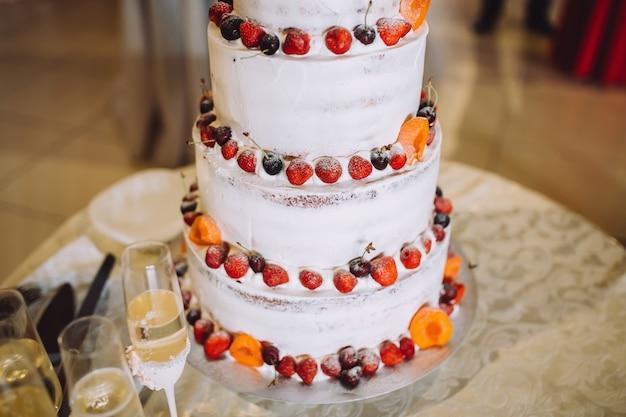 Piękny tort weselny z czerwono-pomarańczowymi owocami.