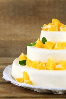 Piękny tort weselny z pomarańczami na drewnianym tle
