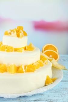 Piękny tort weselny z pomarańczami na jasnym tle