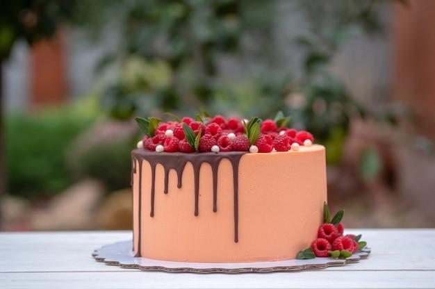 Piękny tort z kremem brzoskwiniowym z malinowymi jagodami i polewą czekoladową