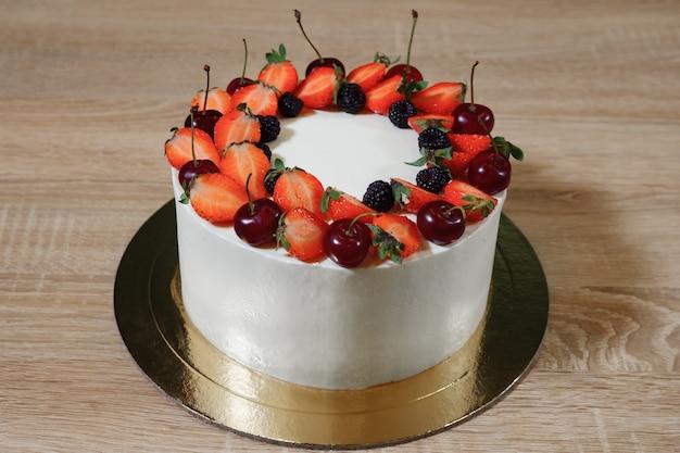 Piękny tort z truskawkami, wiśnią, jeżyną i śmietaną na drewnianym tle.