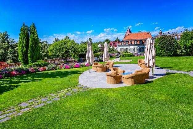 Piękny trawnik z miejscem do relaksu w luksusowym hotelu nad jeziorem lemann. bogata dekoracja.